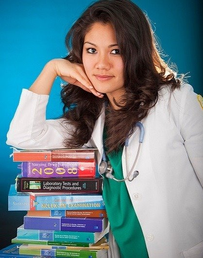 Practical Nursing student studying exam books